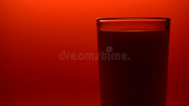 Leite sombreado no fundo vermelho, produtos láteos orgânicos, nutrição saudável imagem de stock