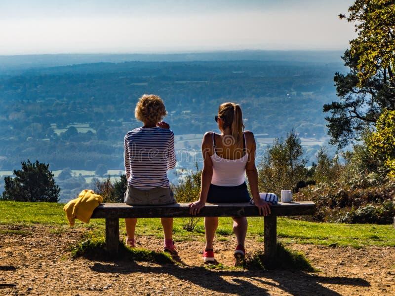 LEITH-KULLE, DORKING, SURREY, ENGLAND - OKTOBER 10, 2018: Två kvinnor på en bänk som dricker och ser sikt royaltyfria foton