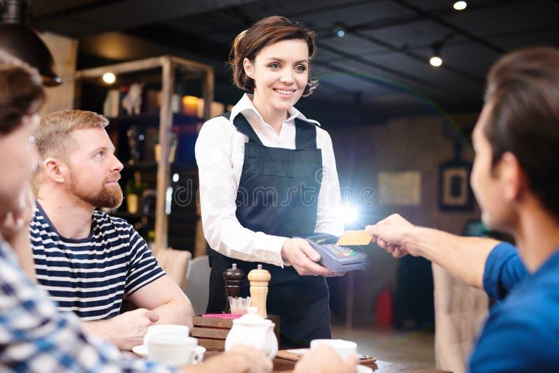 Leitor de cartão feliz da terra arrendada da empregada de mesa da senhora quando convidado que paga com imagens de stock royalty free
