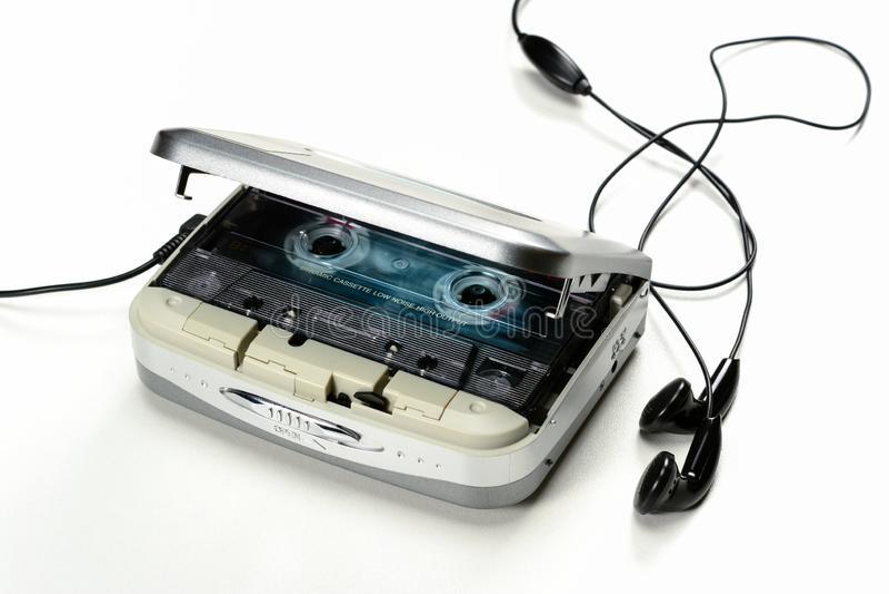 Leitor de cassetes compacto da cassete áudio portátil do vintage com fones de ouvido e gaveta, dispositivo cinzento no fundo bran foto de stock