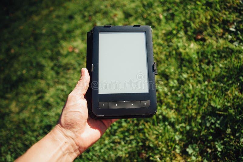Leitor de EBook à disposição, fundo da grama imagens de stock