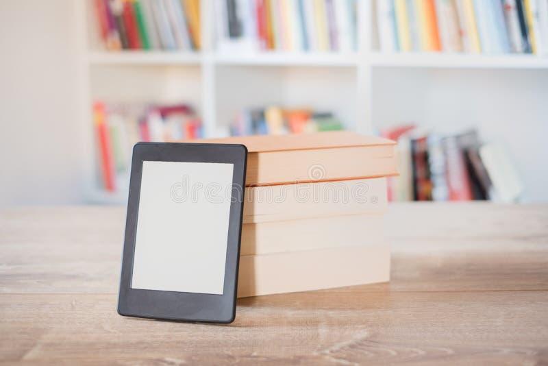 Leitor de EBook em uma pilha de livros imagem de stock royalty free