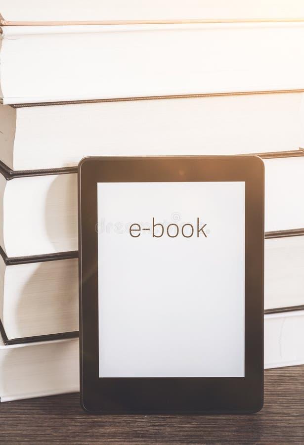 Leitor de EBook em uma pilha de livros fotos de stock royalty free