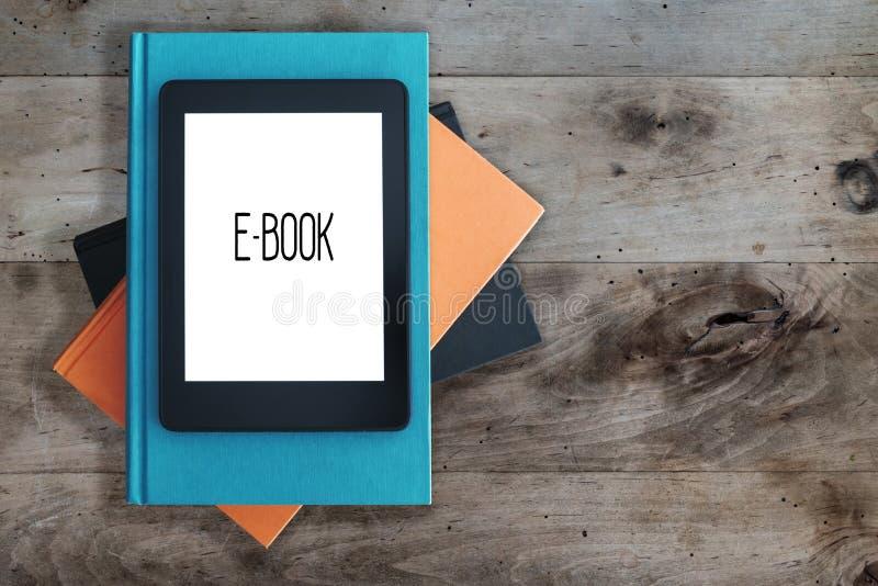 Leitor de EBook em uma pilha de livros no conceito de madeira rústico da tabela fotos de stock royalty free