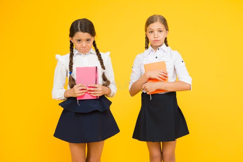 Leitores ávidos infelizes Infeliz poucos alunos no fundo amarelo Meninas pequenas adoráveis com emoções infelizes imagens de stock royalty free