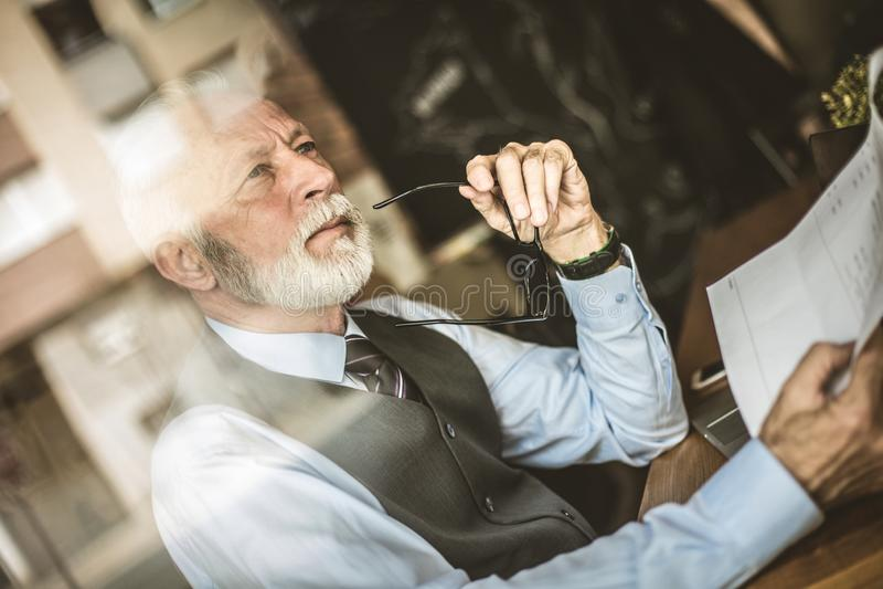leitung Älterer Mann, der mit Dokumenten arbeitet stockfoto