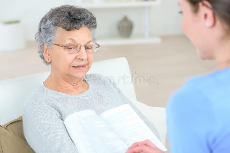 Leitura à pessoa idosa imagens de stock