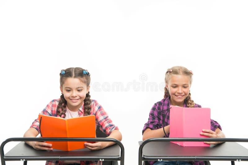 A leitura abre portas Livros de leitura pequenos das crianças isolados no branco As meninas adoráveis aprendem a leitura em preli imagens de stock