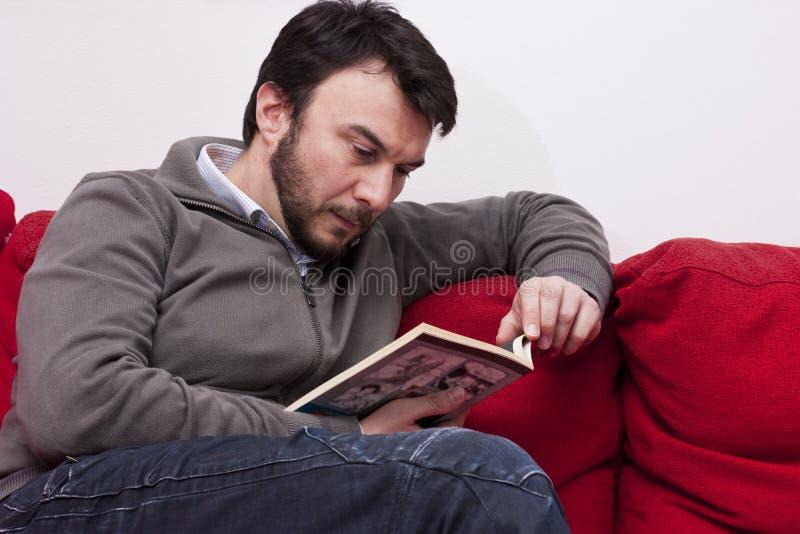 Leitura adulta do homem em casa imagens de stock