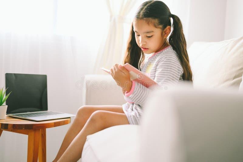 Leitura asiática pequena da menina da criança feliz livros na tabela na sala de visitas em casa conceito da atividade da fam?lia fotografia de stock royalty free