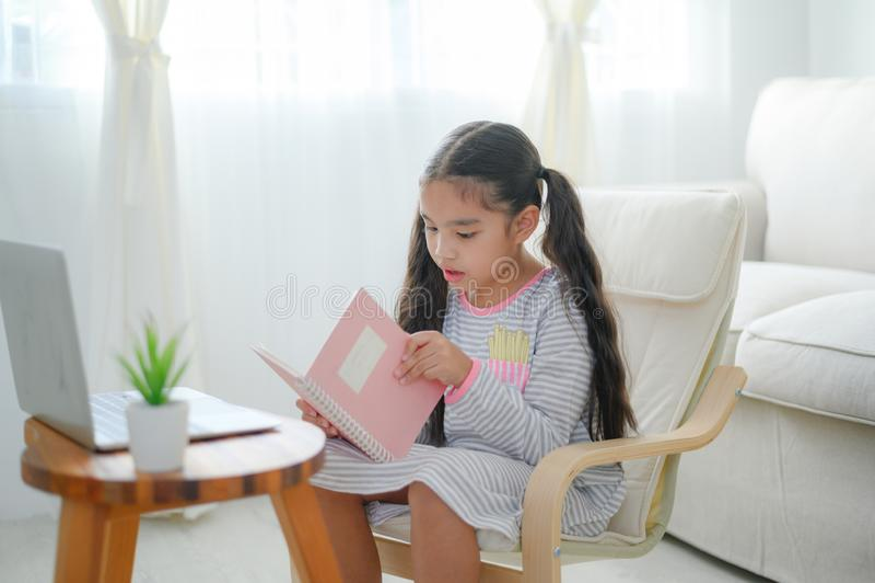 Leitura asiática pequena da menina da criança feliz livros na tabela na sala de visitas em casa conceito da atividade da fam?lia imagem de stock