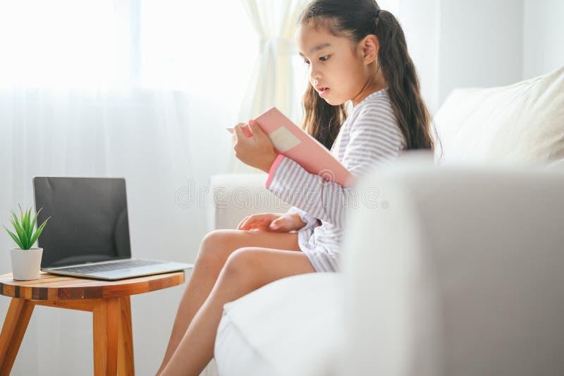 Leitura asiática pequena da menina da criança feliz livros na tabela na sala de visitas em casa conceito da atividade da fam?lia imagens de stock