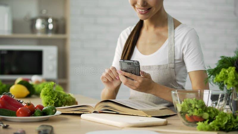 Leitura bonita da mulher que cozinha o livro e calorias calculadoras no smartphone app imagens de stock royalty free