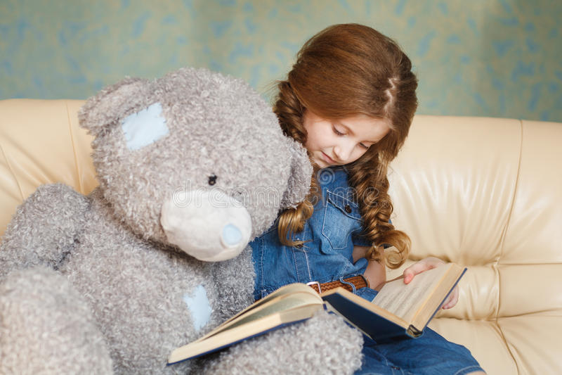 Leitura bonito da menina com urso de peluche imagens de stock royalty free
