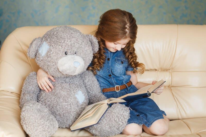 Leitura bonito da menina com urso de peluche fotografia de stock