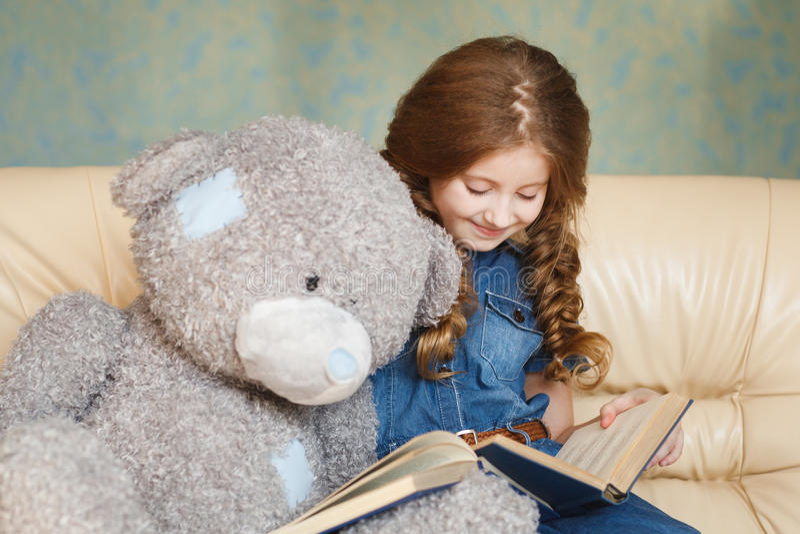 Leitura bonito da menina com urso de peluche foto de stock royalty free