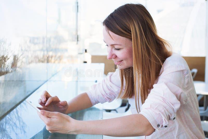 A leitura caucasiano de sorriso da mulher envia por correio eletrónico em linha no tablet pc digital imagem de stock