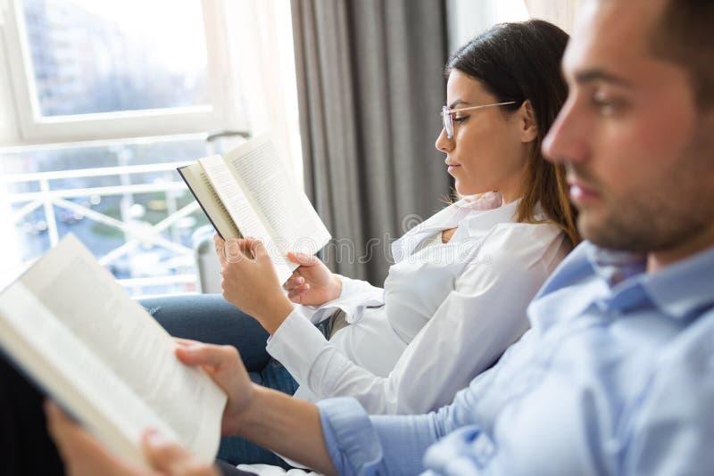 Leitura concentrada atrativa dos pares junto ao relaxar na cama na sala de hotel imagens de stock royalty free