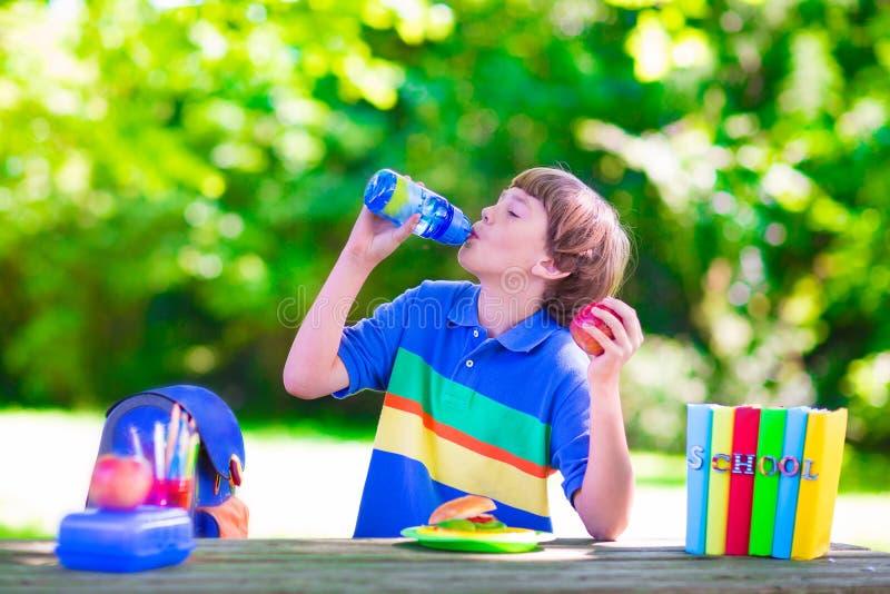 Leitura da criança e sanduíche comer na jarda de escola fotografia de stock royalty free