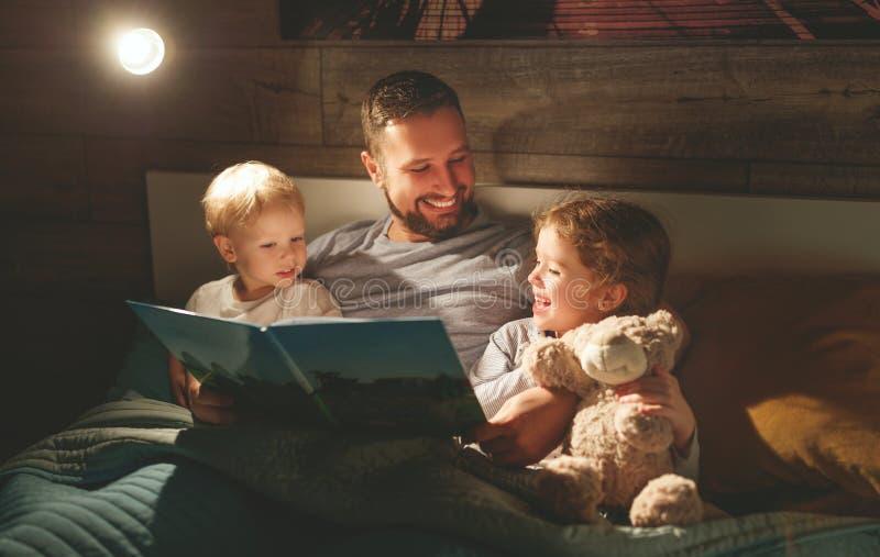 Leitura da família da noite o pai lê crianças livro antes do goin fotografia de stock