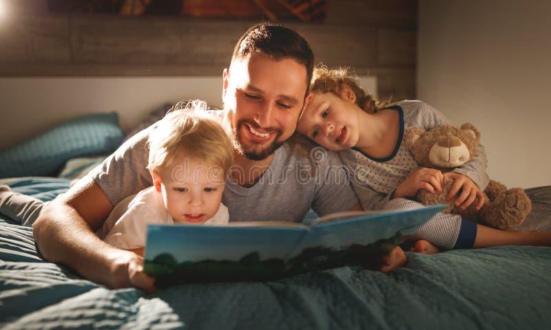 Leitura da família da noite o pai lê crianças livro antes do goin fotos de stock royalty free