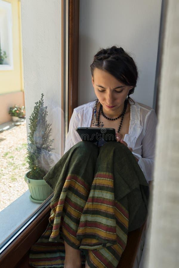 Leitura da jovem mulher de sua tabuleta fotos de stock