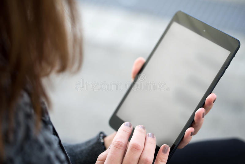 Leitura da jovem mulher na tabuleta fotos de stock royalty free