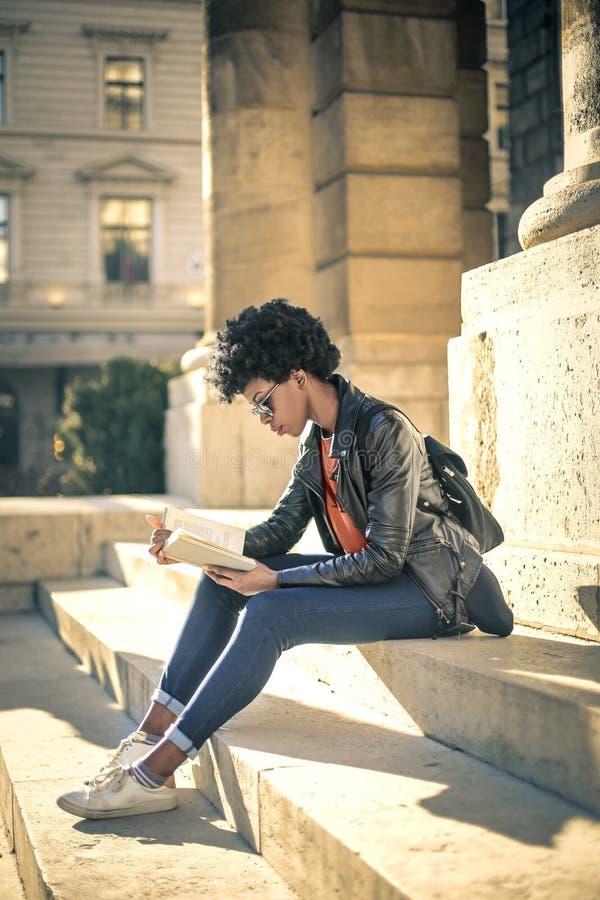 Leitura da jovem mulher nas escadas imagens de stock royalty free
