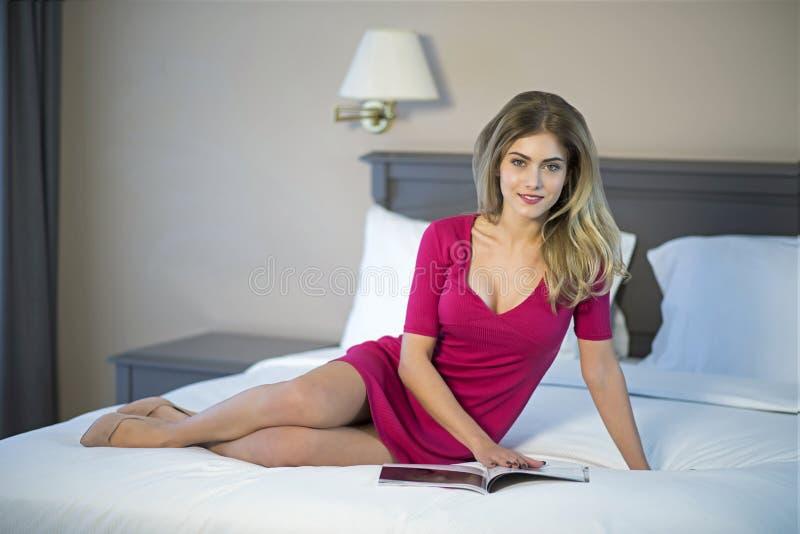Leitura da jovem mulher que relaxa ao ler na cama fotos de stock