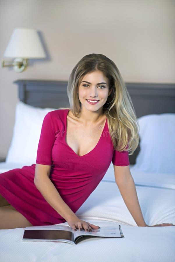 Leitura da jovem mulher que relaxa ao ler na cama imagens de stock