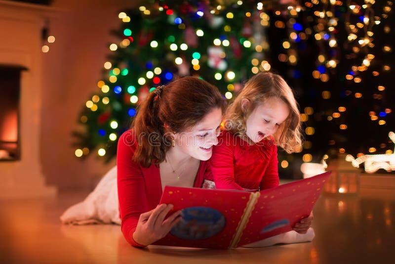 Leitura da mãe e da filha no lugar do fogo na Noite de Natal imagens de stock royalty free