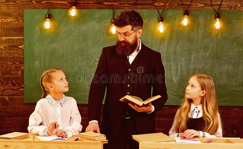 Leitura da mamã com filho irmãs que aprendem a literatura em casa aprendizagem em casa com professor sério aprendendo em casa o c fotos de stock