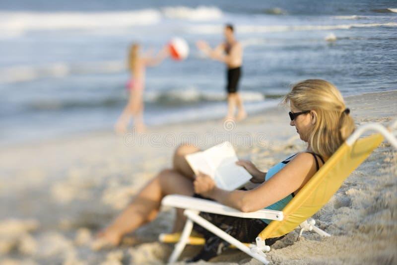 Leitura da mamã na cadeira de sala de estar na praia. foto de stock royalty free