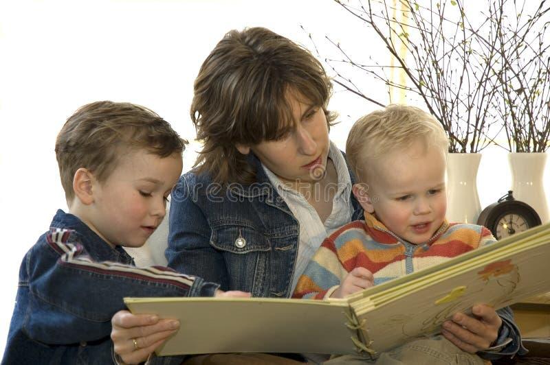 Leitura da matriz e dos dois filhos um livro foto de stock