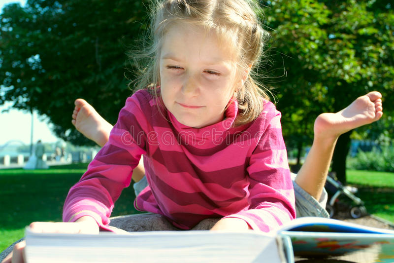Leitura da menina da criança no parque fotos de stock