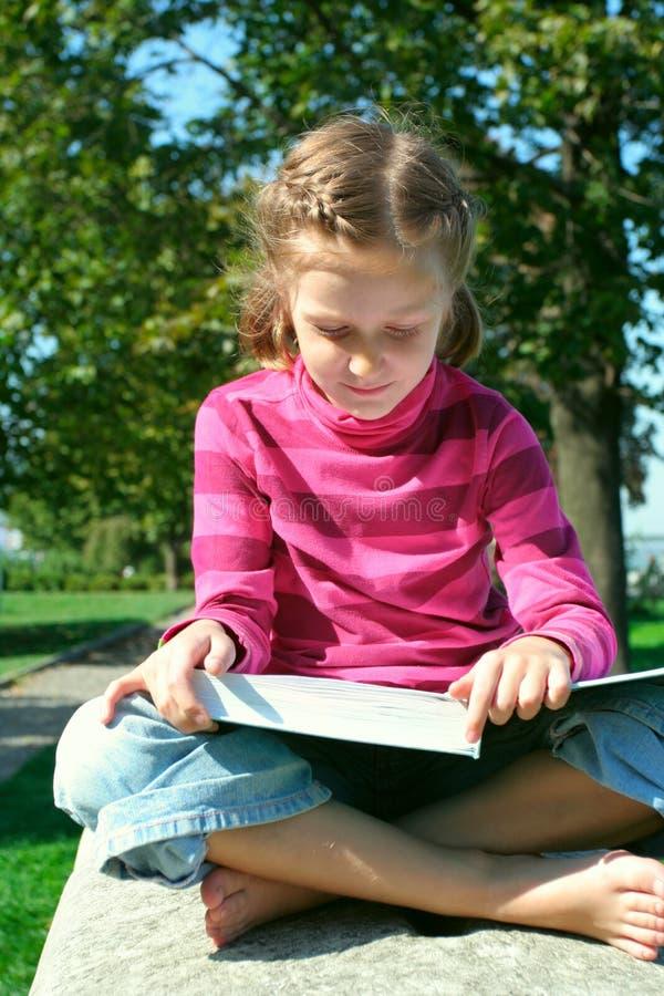 Leitura da menina da criança no parque imagens de stock royalty free