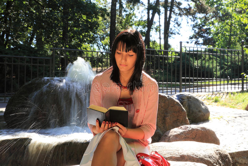 Leitura da menina pela fonte imagem de stock royalty free