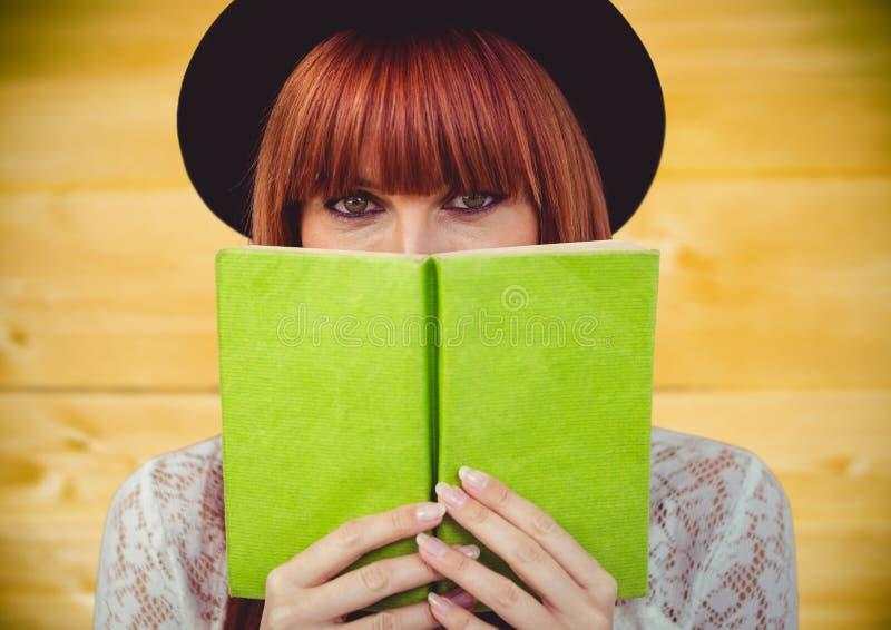 Leitura da mulher contra o painel de madeira amarelo fotos de stock