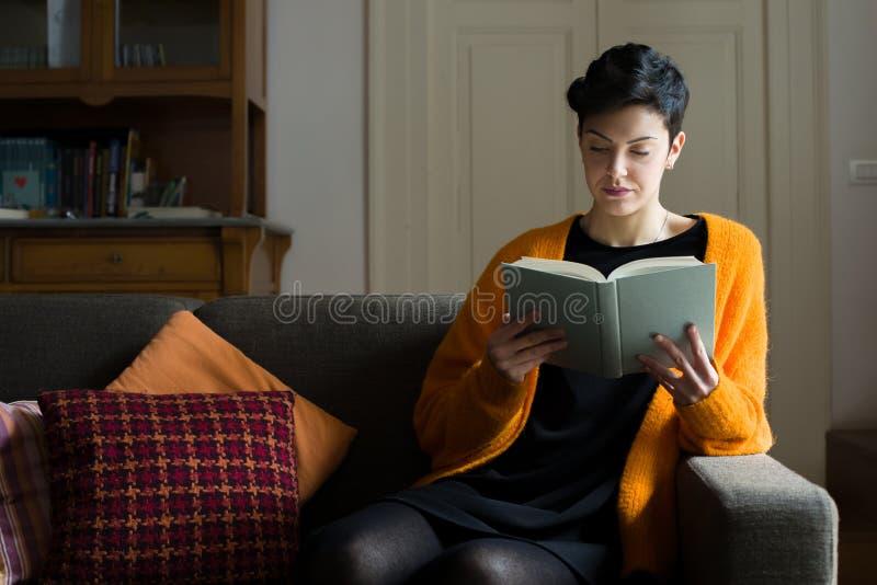 Leitura da mulher em um sofá foto de stock royalty free