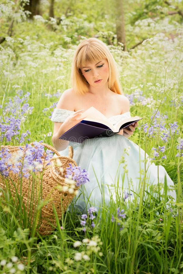 Leitura da mulher no prado da mola fotografia de stock