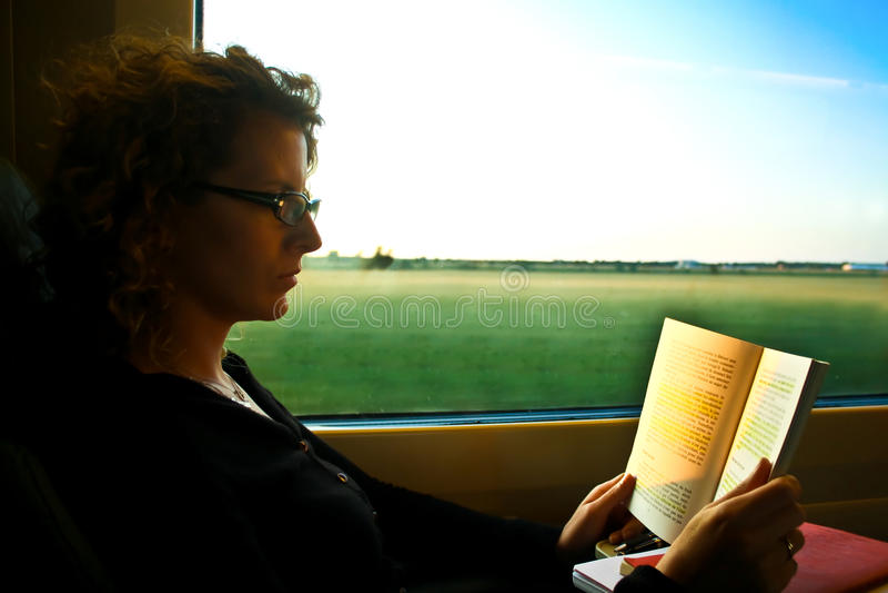 Leitura da mulher no trem imagens de stock royalty free