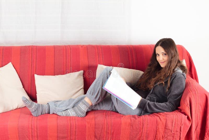 Leitura da mulher nova em um sofá imagens de stock royalty free