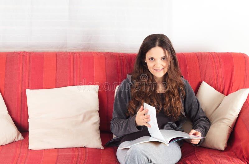 Leitura da mulher nova em um sofá foto de stock