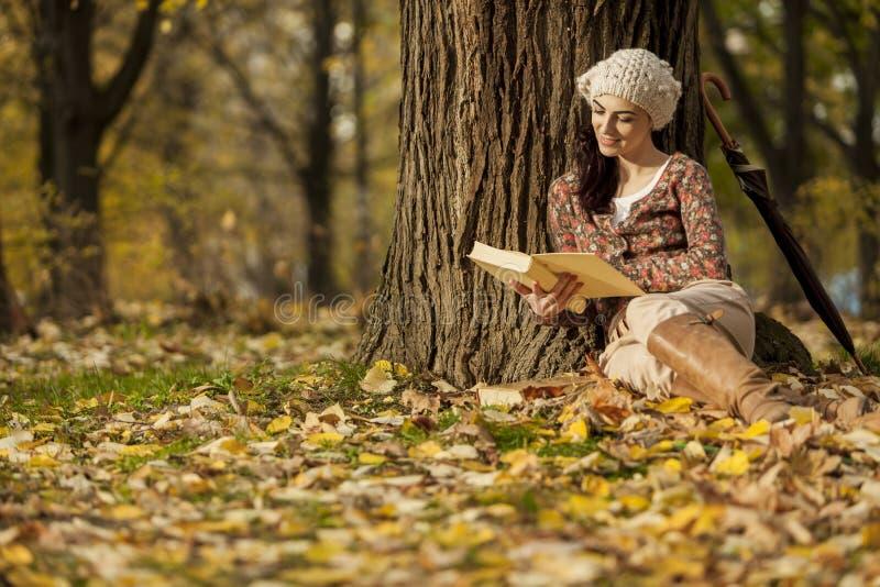Leitura da mulher nova na floresta do outono imagem de stock royalty free