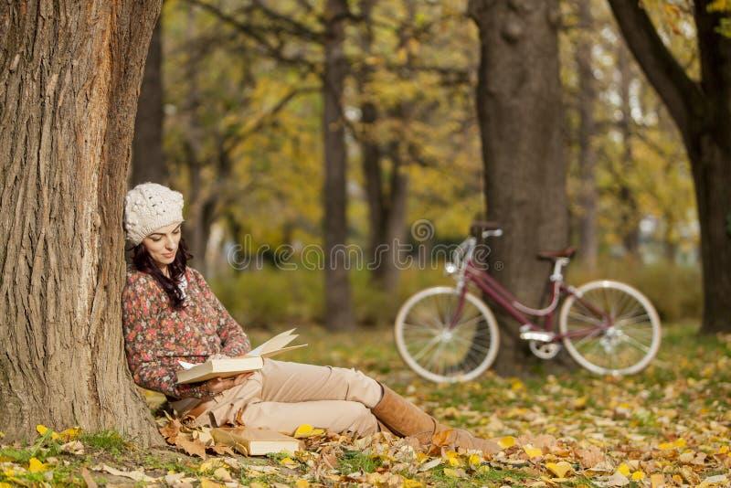 Leitura da mulher nova na floresta do outono imagem de stock