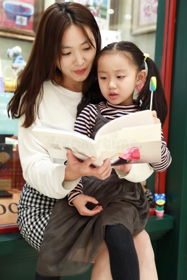 Leitura da prática da menina no mercado brilhantemente iluminado foto de stock royalty free