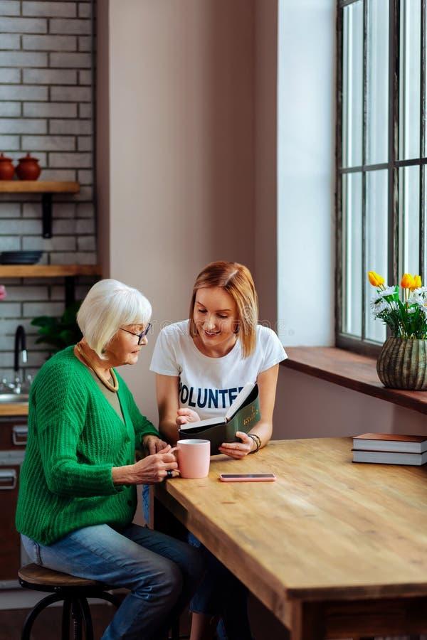 Leitura de sorriso Holly Bible da senhora quando pensionista que escuta ela fotos de stock royalty free