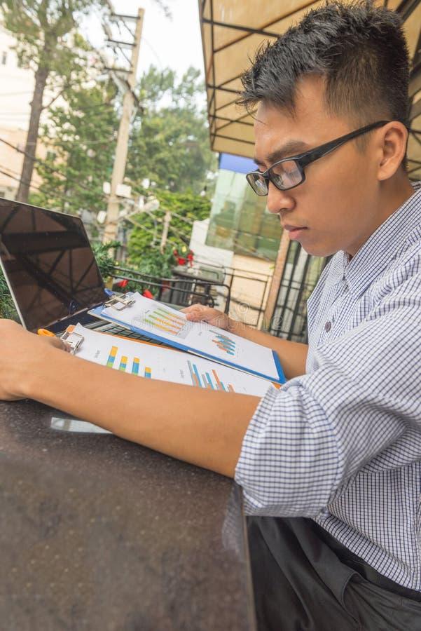 Leitura do empregado de escritório e dados da análise no documento foto de stock