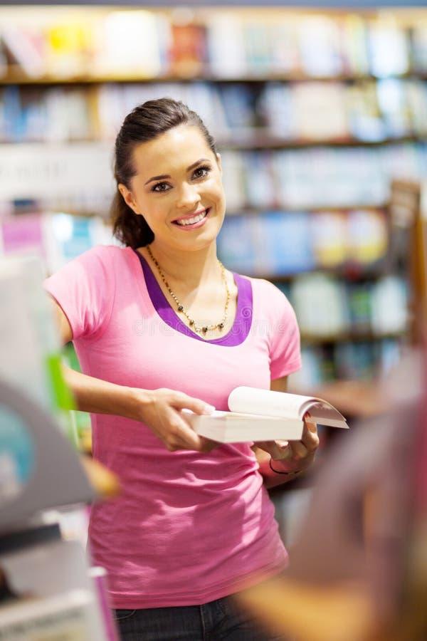 Leitura do estudante universitário na biblioteca foto de stock