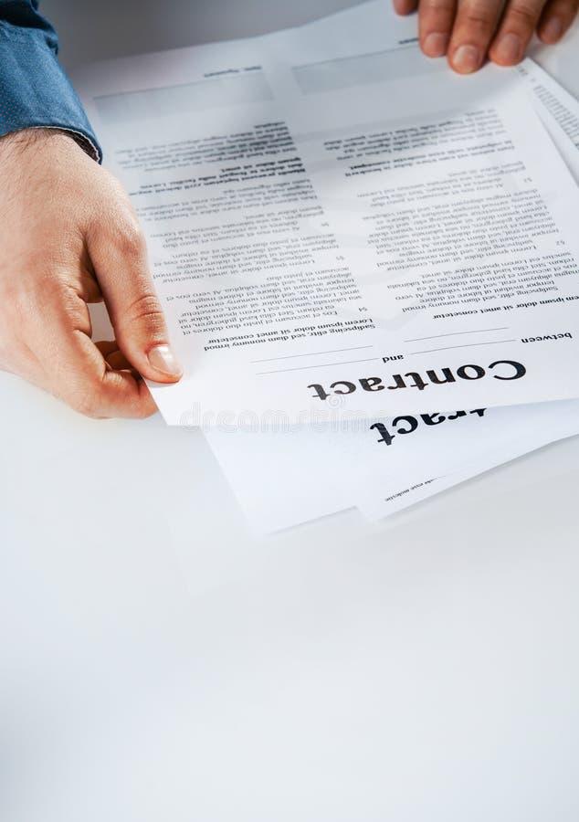 Leitura do homem de negócios através de um contrato imagem de stock